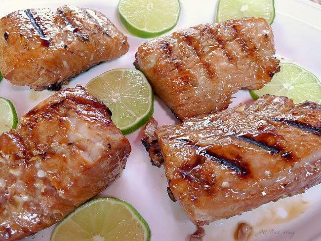 Four grill marked Mahi Mahi fillets on a white platter with lime slices surrounding the fish.