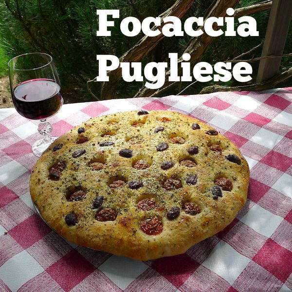 Focaccia Pugliese under the Pergola with la glass of red Wine on top of a red checkered tablecloth.
