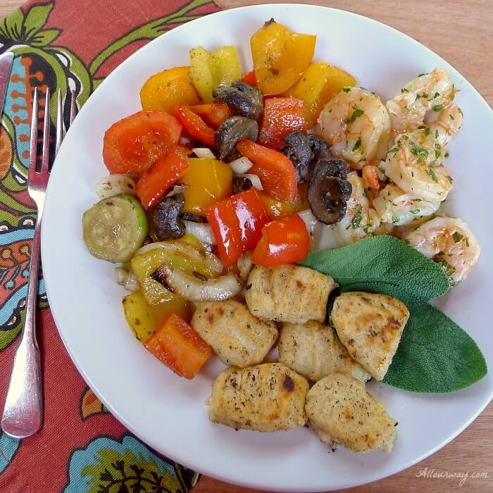 Ricotta Gnocchi with grilled shrimp and peppers on a white plate with a rust and green multi colored napkin@allourway.com
