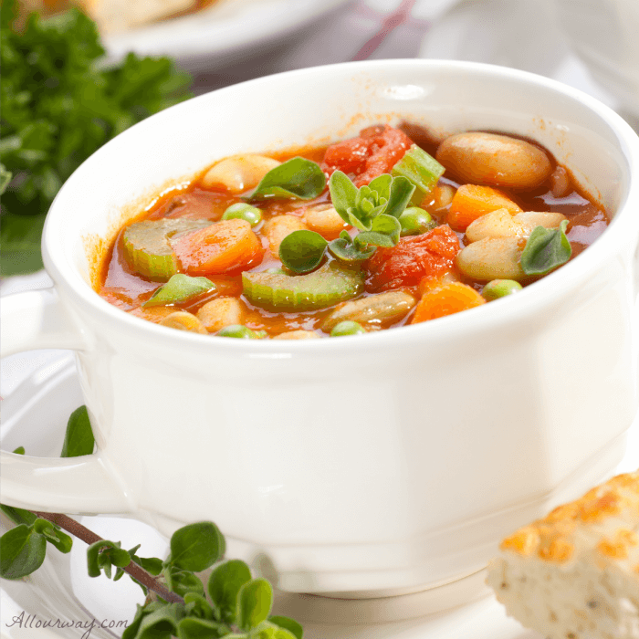 White soup cup filled with Chicken Minestrone Soup with carrot, celery, chicken, peas, tomatoes beans and pasta@ allourway.com