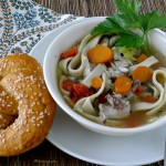 Homemade Chicken Noodle Soup served in a white oversized cup with a Homemade Pretzel next to it and a black and blue print napkin next to it. @allourway.com