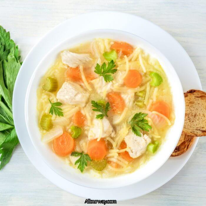 Rich chicken broth with chunks of chicken, carrots, celery noodles and parsley leaves on top.