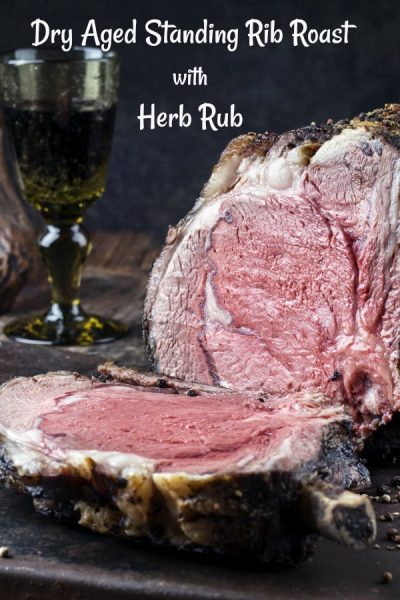 Standing Rib Roast cooked to medium rare with a slice on the wooden board.