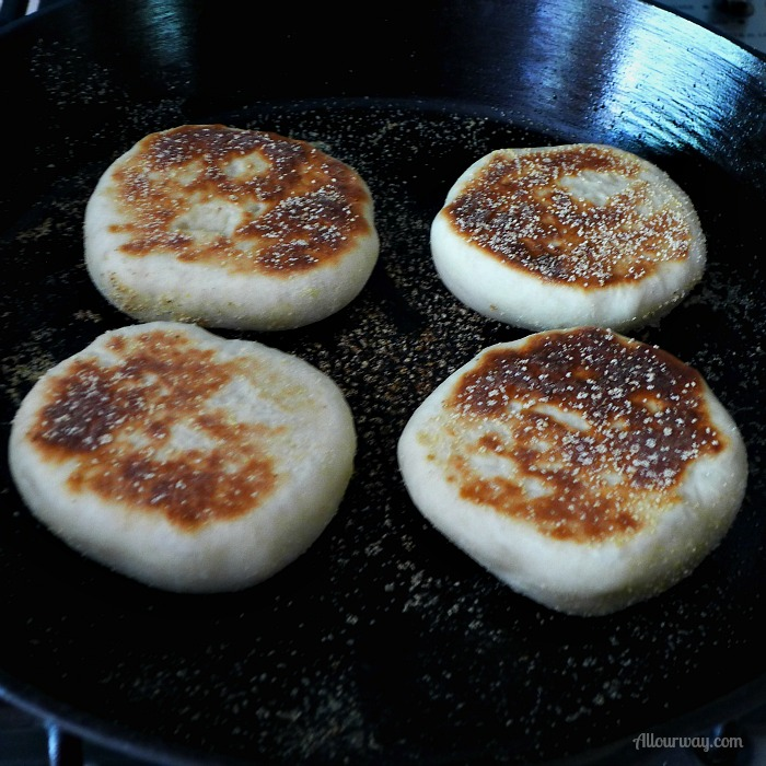 English Muffins cooking in a black cast iron skillet. They are already browned on one side.