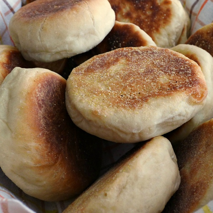 Close up of browned English Muffins in a towel lined basket.
