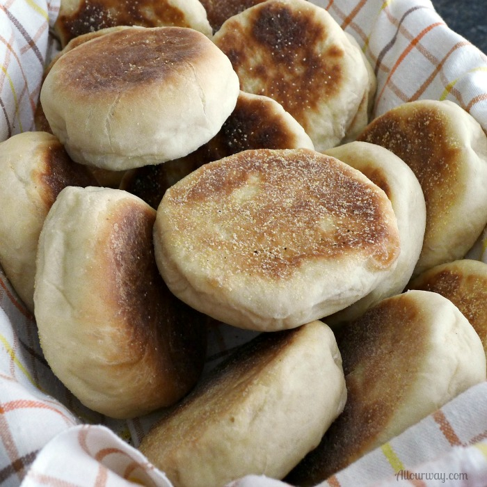 English Muffins piled on a brown orange yellow plaid towel lined bread basket.