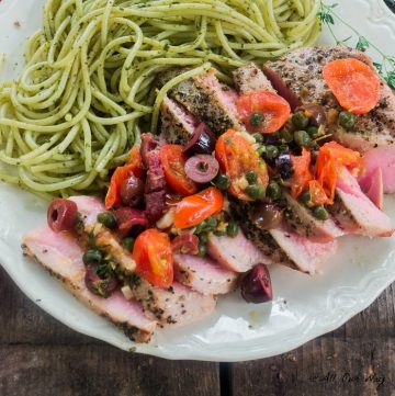 Southern Italian Grilled Tuna Steaks with a fresh grape tomato and black olive sauce to top the delicious sliced medium rare tuna along with green pesto pasta.