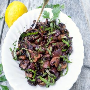 Lemon Herb Roasted Mushrooms in a white platter with basil ribbons on top and a lemon on the side. @ Allourway.com