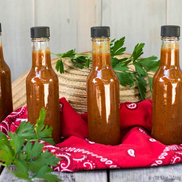 Close up of three small bottles or red Light My Fire Habanero Pepper Sauce that's sitting on a red bandana, straw hat, and two sprigs of green parsley.i