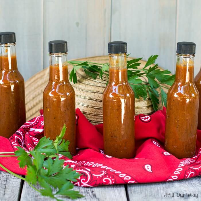 Four bottles of red habanero hot sauce on a red bandana handkerchief that is sitting on a straw hat with 2 sprigs of green parsley.