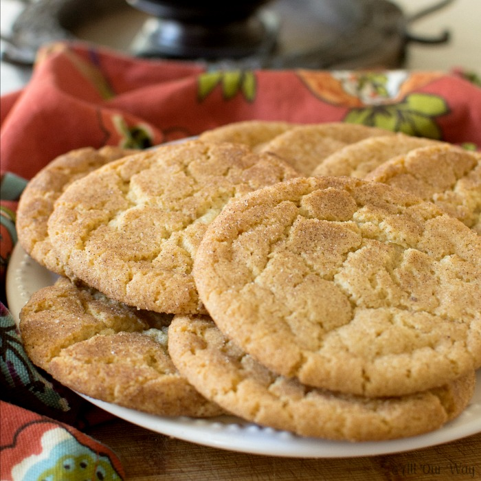 Brown Butter Snickerdoodle Cookies on a white plate with a burnt orange napkin on the side.