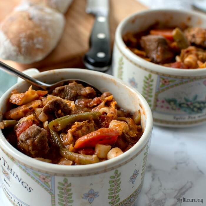 Two bowls of Rustic Italian Vegetable Beef Stew with a loaf of bread on a wooden cutting board and a knife on the side.
