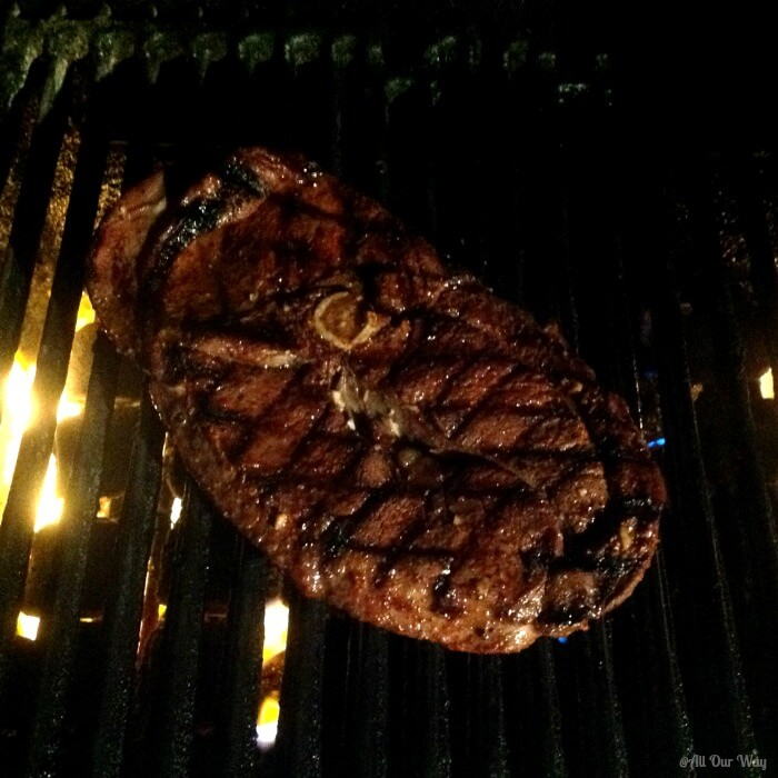 Venison steak over a hot fire on a black grill.