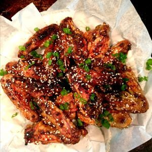 Spicy Teriyaki Chicken Wings Are Finger Licking Good are rich with glaze and on a white piece of parchments paper.