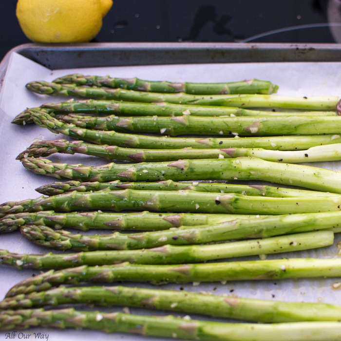 Roasted Lemon Garlic Asparagus with Parmesan on a parchment lined baking sheet.