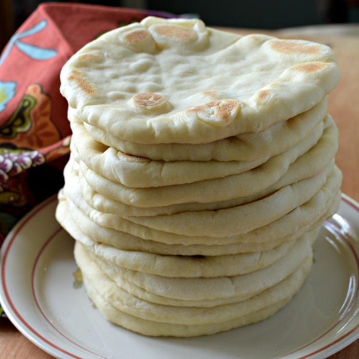 Flatbread is stacked up one on top of each other on a white plate with russet edge. A brick colored napkin with turquoise and gold is on the side.