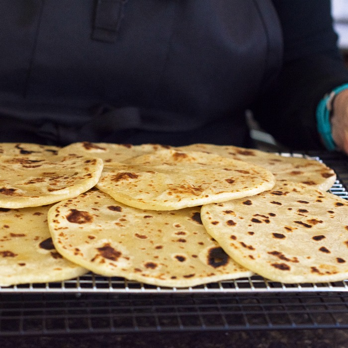 A woman holding a rack full of Flatbread rounds that are cooked