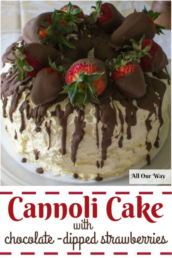 Whipped cream frosted cannoli cake with a chocolate glaze on top and chocolate strawberries.