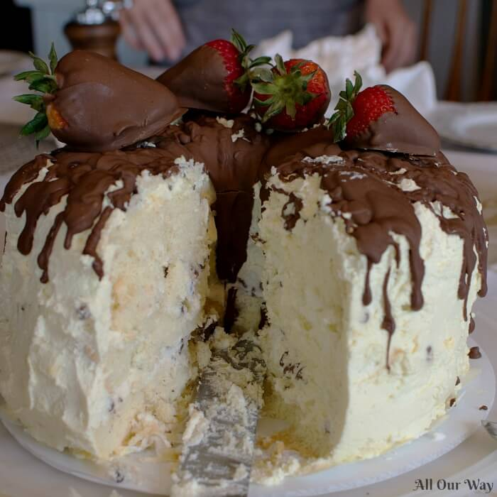 Cannoli cake filled with sweetened ricotta cheese and chocolate chips, frosted with whipped cream and chocolate-dipped strawberries.