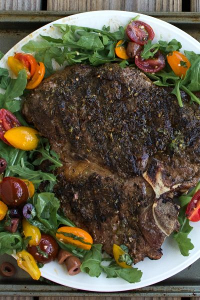 Grilled Porterhouse Steak Sicilian Style with Marinated Cherry Tomatoes over Arugula.