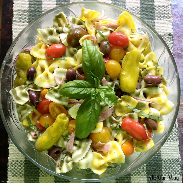 Lemon Basil Farfalle Salad in a glass bowl. A combination of striped bow pasta, grape tomatoes, hot peppers, black olives, mozzarella cubes
