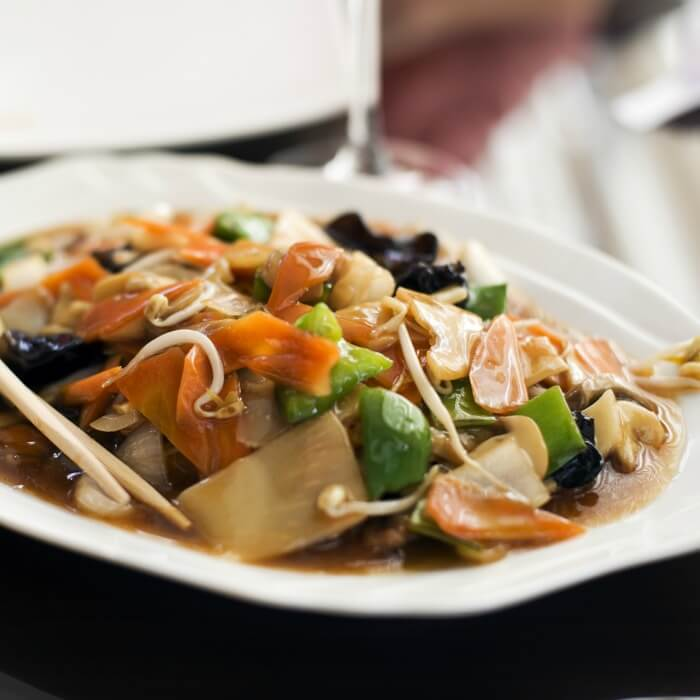 Chicken Chop Suey in a white bowl. The recipe is very adaptable to any meat and vegetable using carrots, green peppers, bean sprouts.