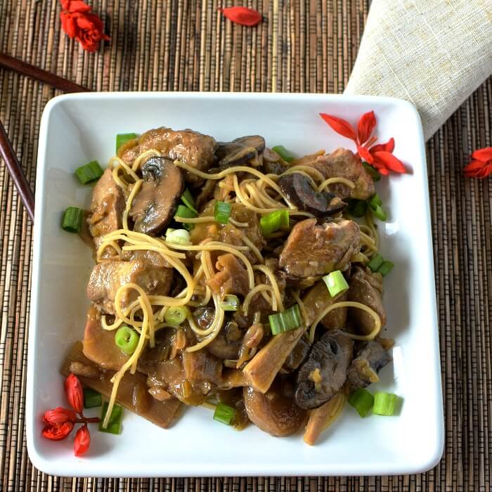 Chop Suey is a Chinese-American Stew with thin pasta and sprinkled with green onions on a white square plate with red salvia blossoms sprinkled around the plate and brown bamboo placemat with a tan linen placement on the side.