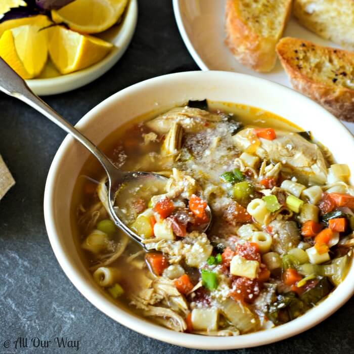 Close of soup in bowl with spoon, Roasted chicken vegetable soup with pasta, lemon wedges and bread on table