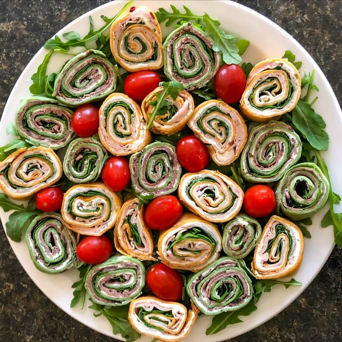Red and Green Tortilla pinwheels on a white platter with red cherry tomatoes and a sprinkling of green arugula around the platter.