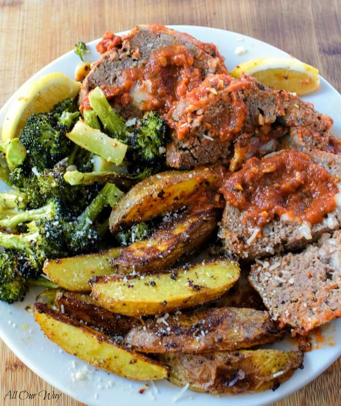 Polpettone Italian stuffed meatloaf on white plate with broccoli, wedged baked potatoes and slivers of lemon.
