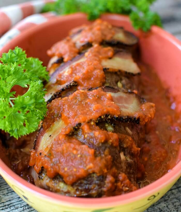 Polpettone Italian stuffed meatloaf is a red casserole dish with green parsley on the side. Bacon and marinara sauce tops the meatloaf.