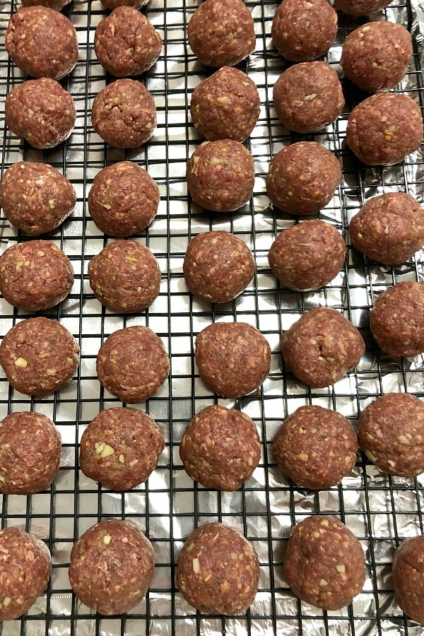 Rows of baked venison meatballs on top of a black wire rack over a foil-lined tray.