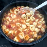 Large pot of Chicken Spinach Tortellini Soup simmering. Large white spoon in pot stirring in the cheese tortellini.