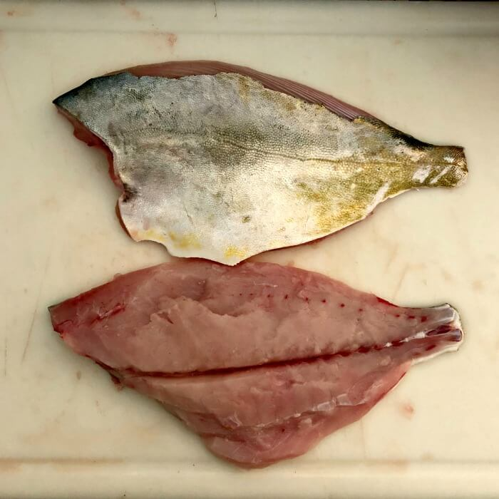 Two Florida Pompano fillets on white cutting board.