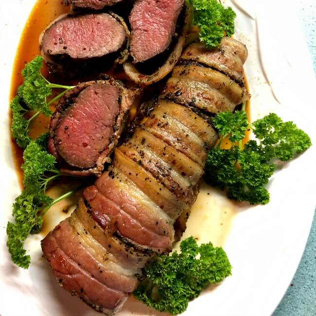 grilled antelope tenderloin is bacon-wrapped with several slices on a white plate with parsley.