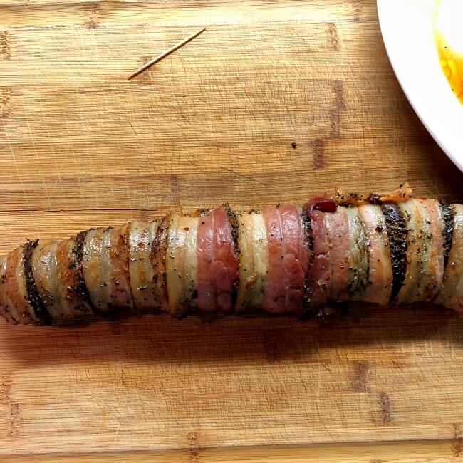 Grilled antelope tenderloin is bacon-wrapped and on cutting board resting before slicing.