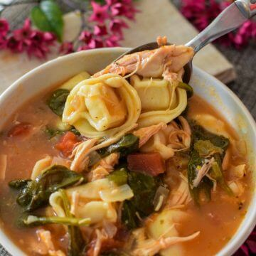 Bowl of chicken spinach tortellini soup with a spoonful of tortellini. Purple flowers in background.