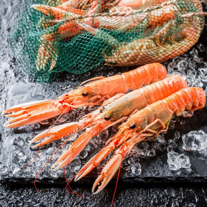 Three orange pink scampi which look like small lobsters on black slate with a sack of scampi in the background.