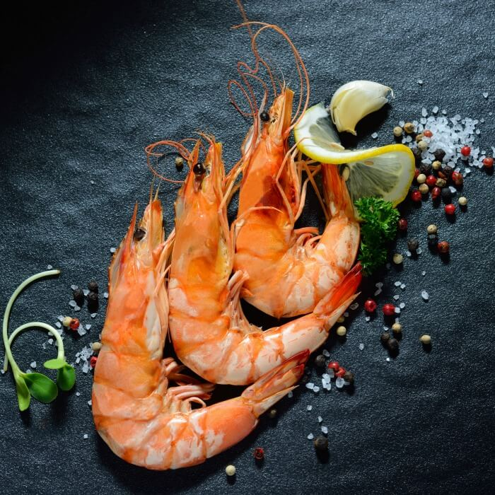 Three large cooked shrimp on black slate stone with sliced lime and peppers strewn around.