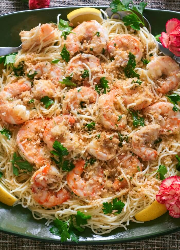 Easy shrimp scampi on a bed of angel hair pasta served on a platter with parsley and lemon with pink flowers in scene.