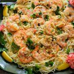 Easy shrimp scampi served over angel hair pasta served on a green platter with lemon slices and pink carnation.
