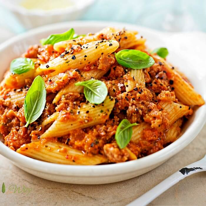 A closeup of Italian sausage penne pasta in a white bowl with a sprinkle of fresh peppercorns and green basil leaves.