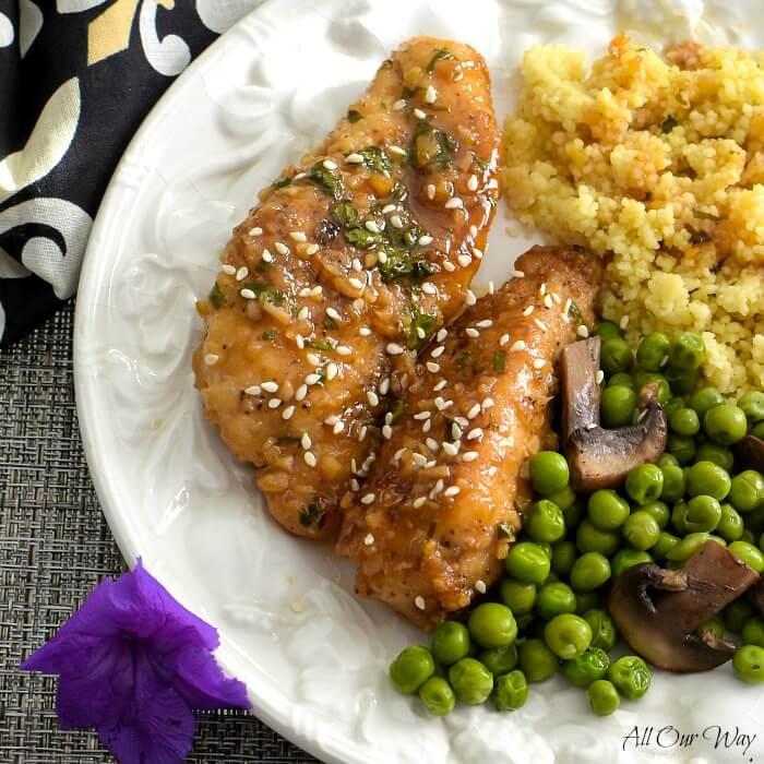 Close up of two honey glazed chicken tenders along with golden quinoa and peas with mushrooms all on a white edge embossed plate. A purple blossom is on the lower left hand edge of the plate and a black napkin with white fleur de lis on the upper left side.