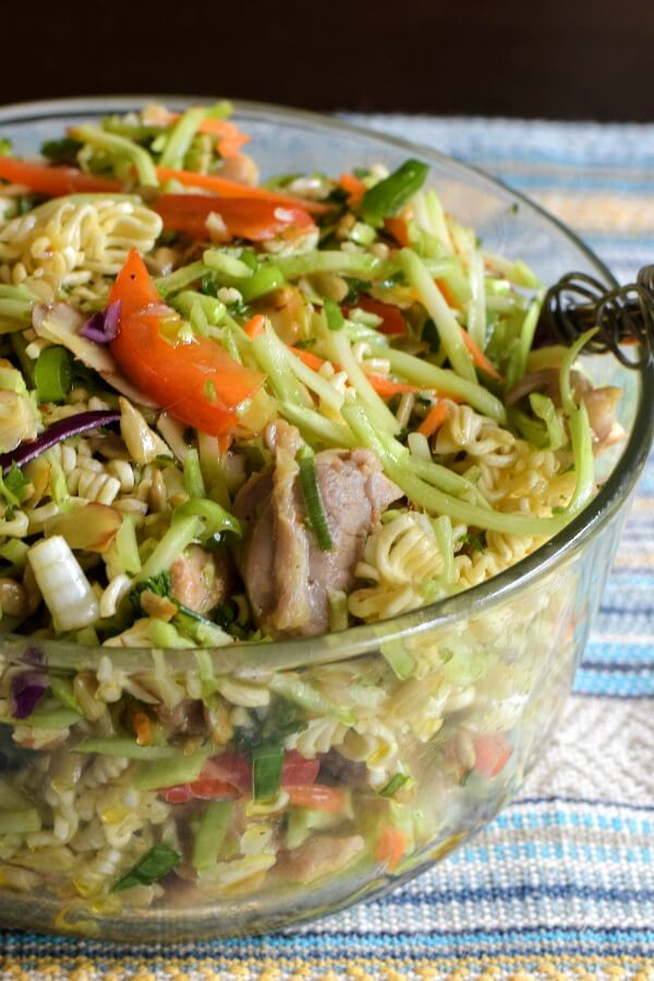 A closeup of a clear glass bowl filled with Ramen Broccoli Slaw Recipe with red pepper matchsticks and chicken pieces top.