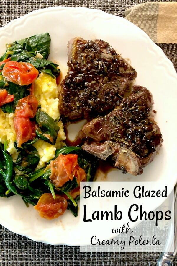 Two lambchops, yellow polenta, grape tomatoes, and baby spinach on a white plate.