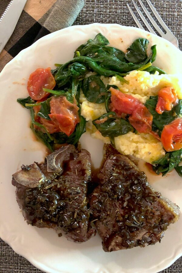 Two balsamic glazed lamb chops on a white plate with yellow polenta and sautéed baby spinach and grape tomatoes on top.