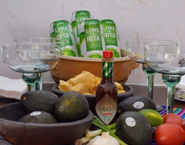 Snack table with avocados, green margarita glasses, TABASCO® Sauce, green and white aluminum cans chilling in a brown pottery bowl of ice.
