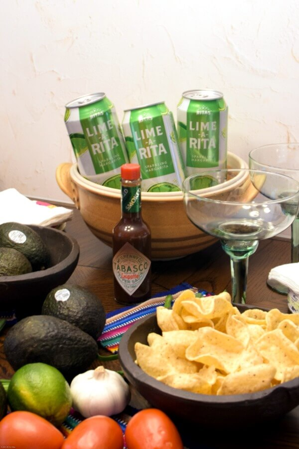 A wooden party table with avocados, tortilla scooper chips, green and white cans chilling in brown pottery pot, a green margarita glass and a bottle of TABASCO® Chipotle Sauce.