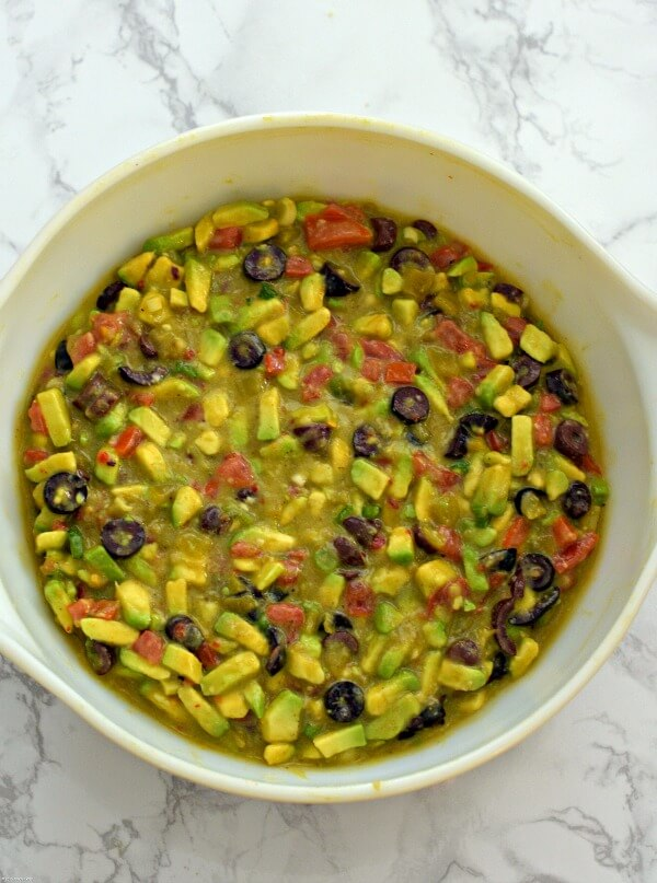 A large white bowl filled with Italian avocado salsa with the addition of tomatoes, black olives, green chilies and onions.
