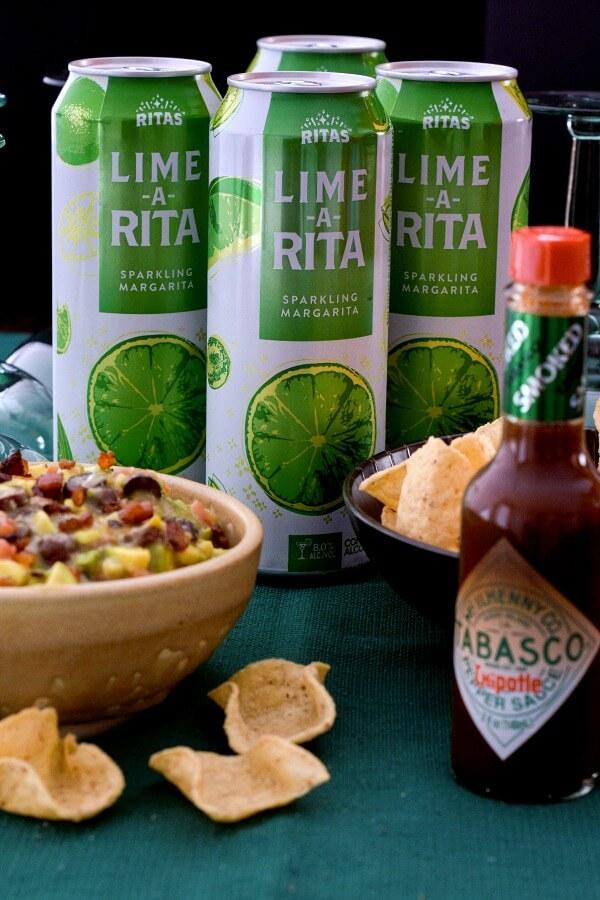 Tan pottery bowl holds Italian avocado salsa, 3 green and white aluminum cans of Lime-A-Rita , bottle of TABASCO® Chipotle Sauce and bowl of tortilla chips on a green tablecloth.